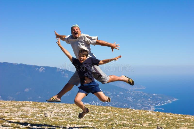 Lycklig man- och pojkebanhoppning på en sky fotografering för bildbyråer