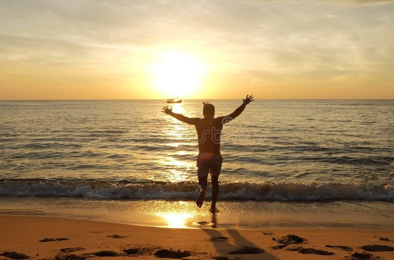 Lycklig man på stranden som kör till havet på solnedgången arkivbilder