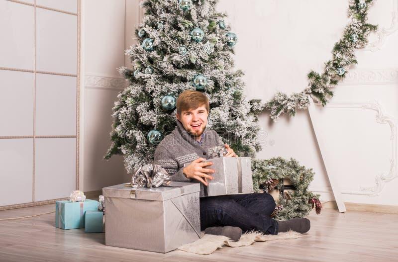 Lycklig man som öppnar ett hemmastatt near julträd för gåva royaltyfria bilder