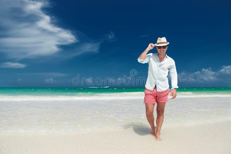 Lycklig man som överför hans hälsningar, medan gå på stranden royaltyfria bilder
