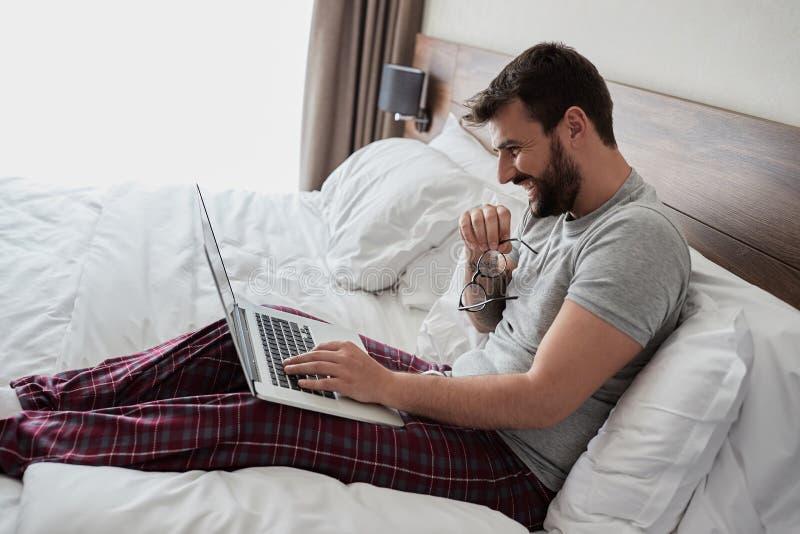 Lycklig man som använder bärbar datordatoren, medan sitta i säng royaltyfri fotografi