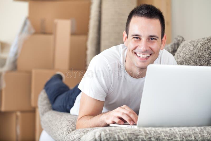 Lycklig man som använder bärbara datorn i hans nya hem fotografering för bildbyråer