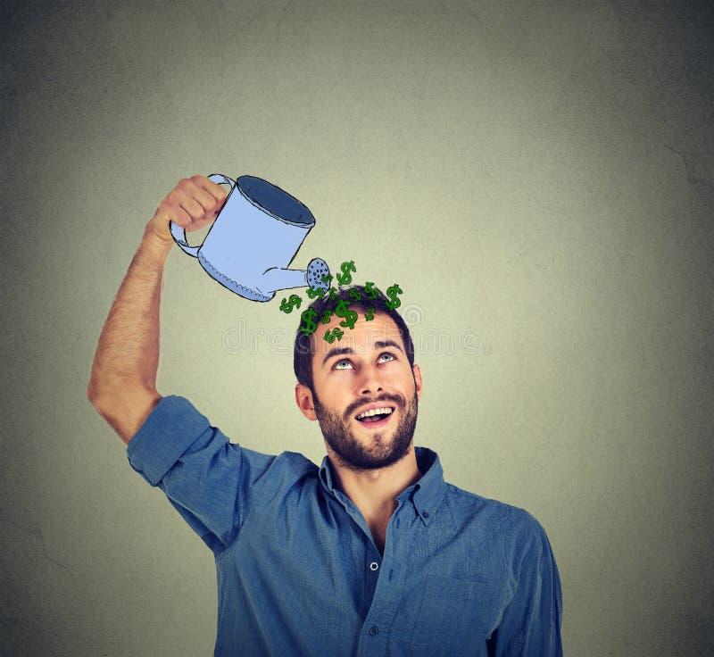 Lycklig man som bevattnar sig med pengar arkivbild