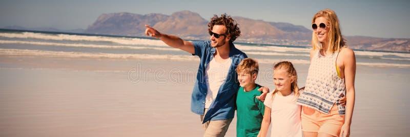 Lycklig man som bort pekar med familjen som går på stranden royaltyfri foto