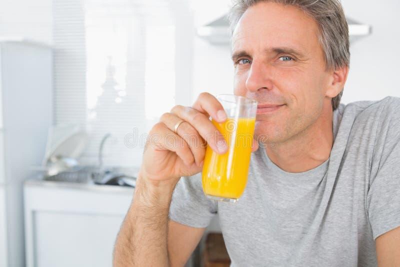 Lycklig man som dricker orange fruktsaft i kök arkivfoto