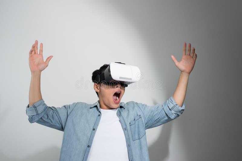 Lycklig man som f?r erfarenhet genom att anv?nda VR-h?rlurar med mikrofonexponeringsglas av virtuell verklighet som isoleras p? v arkivfoton