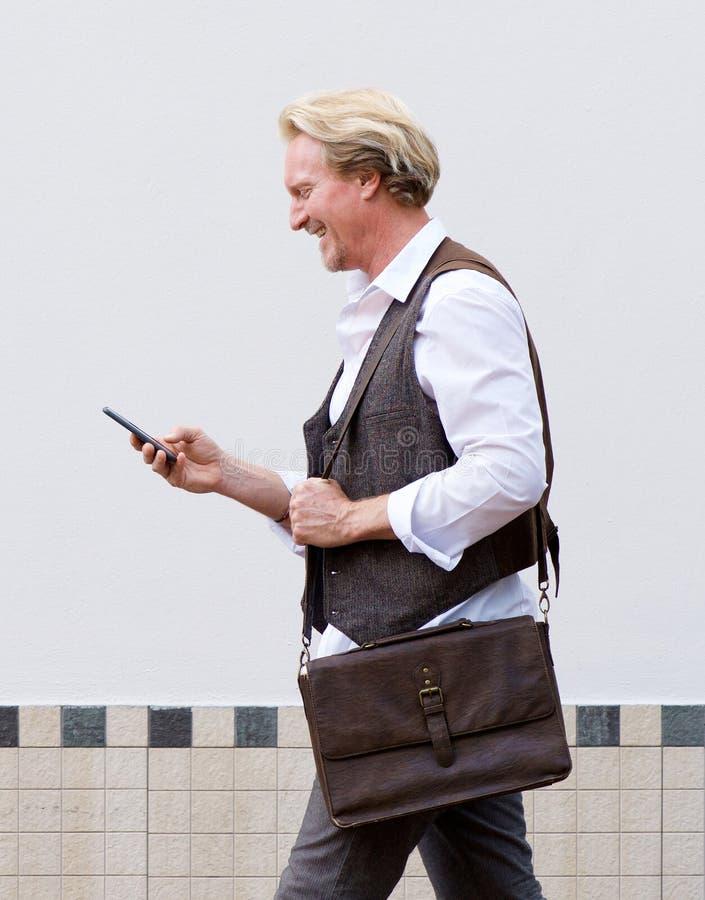 Lycklig man som går med mobiltelefonen och påsen royaltyfria bilder