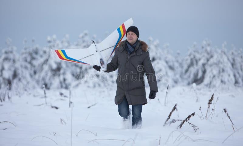 Lycklig man som går på snövinter med rcnivåmodellen arkivfoton