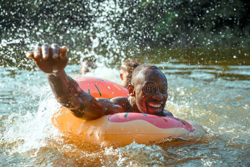 Lycklig man som har roligt, laughting och simmar i floden arkivbilder