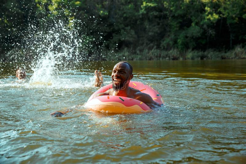 Lycklig man som har roligt, laughting och simmar i floden arkivfoton