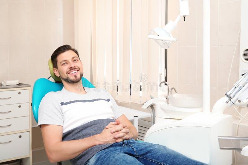 Lycklig man som har tandläkares tidsbeställning i modern klinik royaltyfri foto