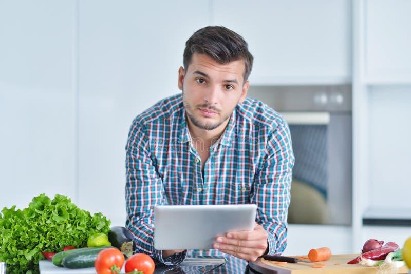 Lycklig man som hemma använder den digitala minnestavlan i kök arkivfoto