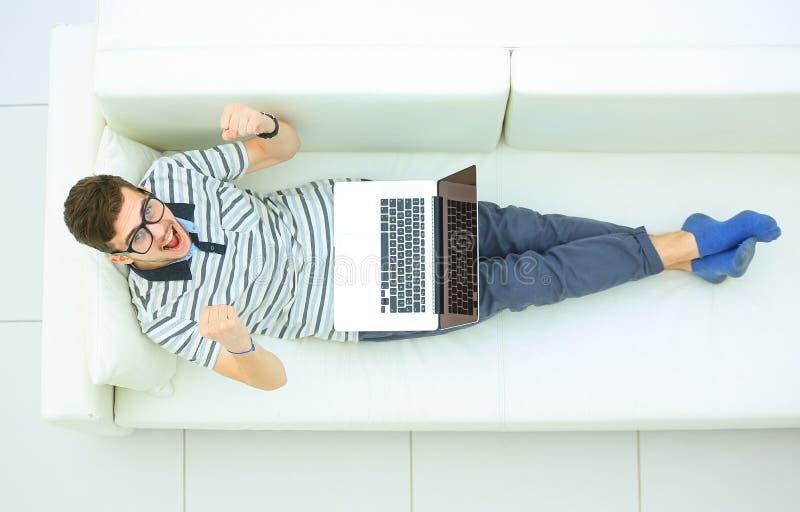 Lycklig man som hemma arbetar på hans bärbar dator på soffan royaltyfria bilder