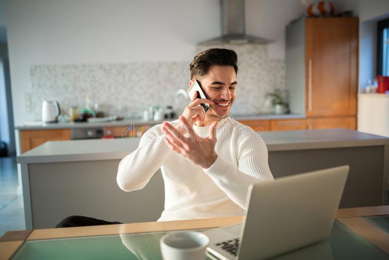 Lycklig man som hemma arbetar samtal på mobil royaltyfri bild