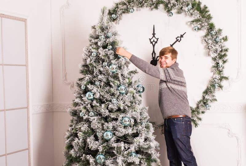 lycklig man som hemma dekorerar julgranen arkivbild