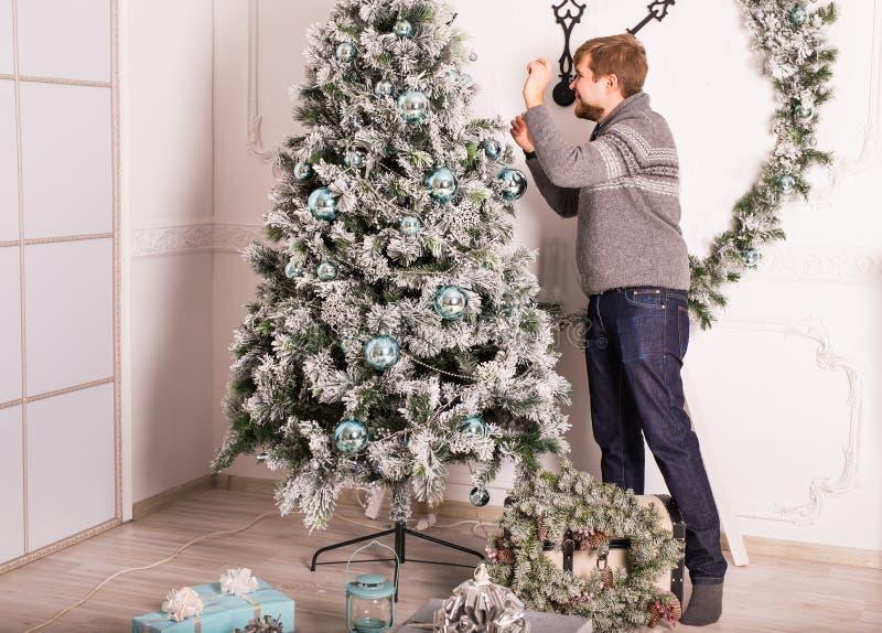 lycklig man som hemma dekorerar julgranen royaltyfria bilder