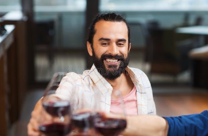 Lycklig man som klirrar exponeringsglas av vin på restaurangen royaltyfri foto