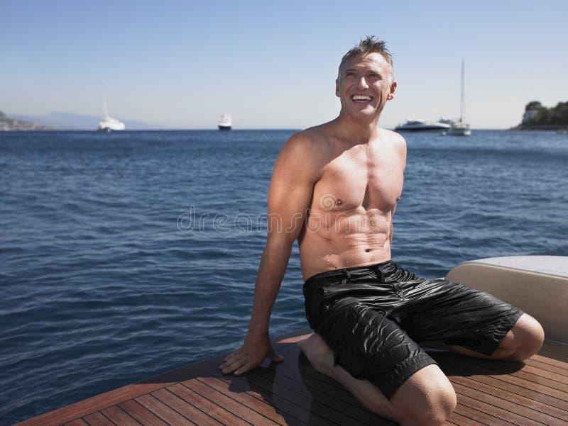 Lycklig man som knäfaller på yachts golvtilja royaltyfri fotografi