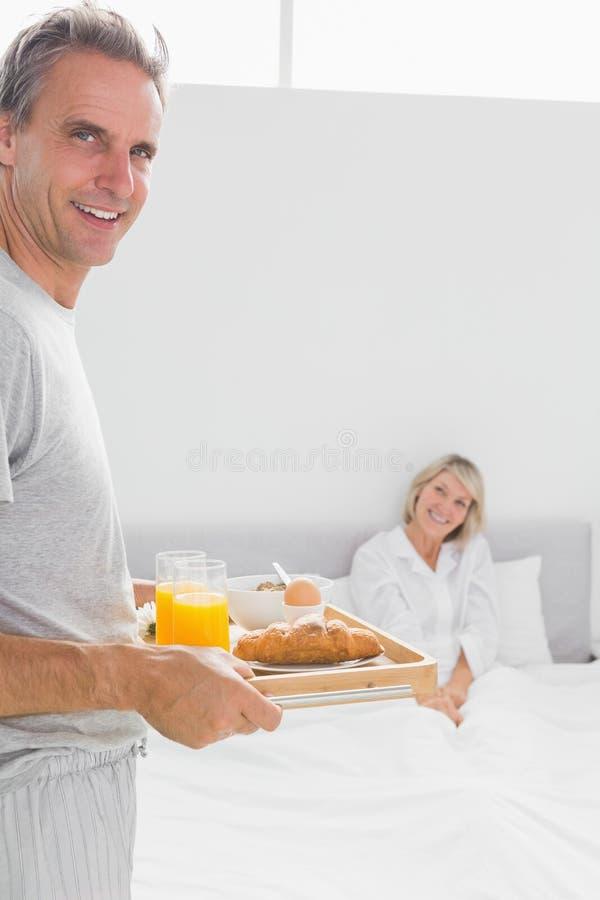 Lycklig man som kommer med frukosten i säng till hans partner arkivbild