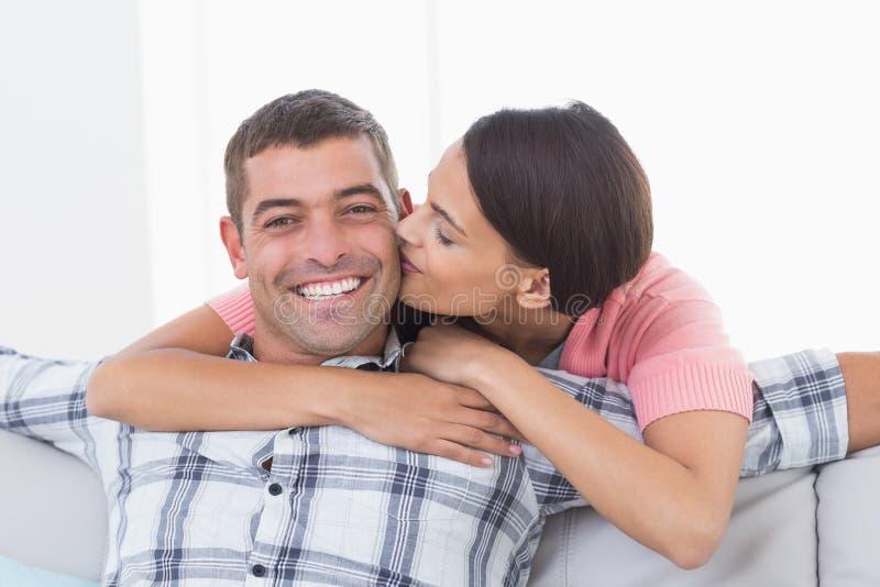Lycklig man som kyssas av kvinnan arkivbilder