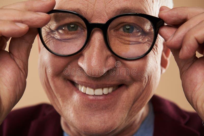 Lycklig man som ler med hans vita tänder, medan bära exponeringsglas arkivfoton