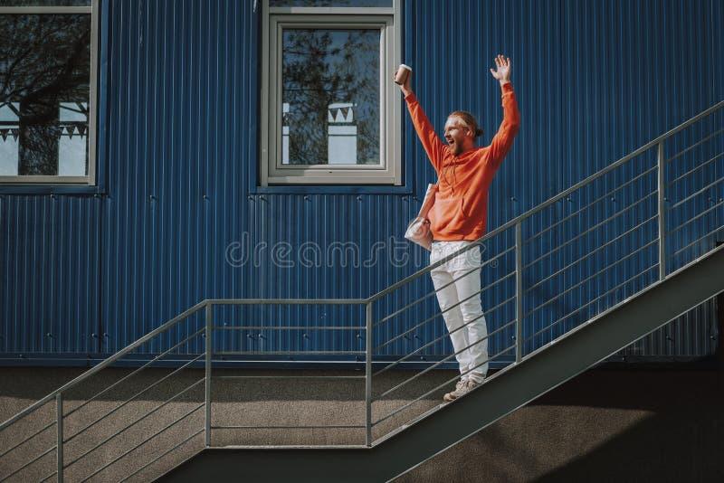 Lycklig man som rymmer h?nder upp p? utomhus- trappa arkivfoton
