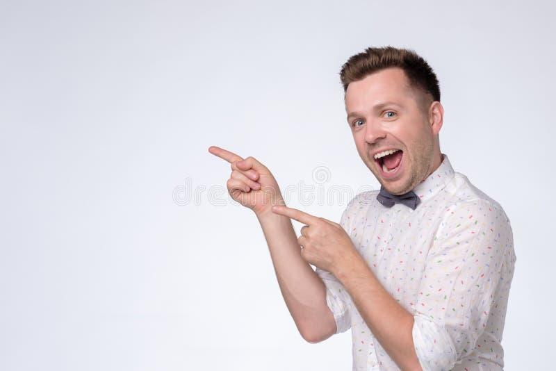 Lycklig man som ser kameran, åt sidan ler och pekar med handen arkivbild