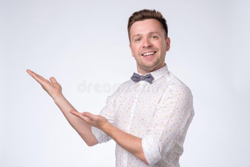 Lycklig man som ser kameran, åt sidan ler och pekar med handen arkivfoton