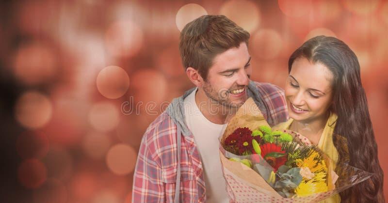 Lycklig man som ser kvinnan med blommor över bokeh arkivbild