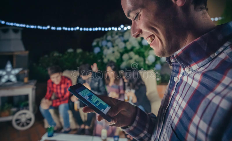 Lycklig man som ser smartphonen i ett parti med vänner royaltyfria foton