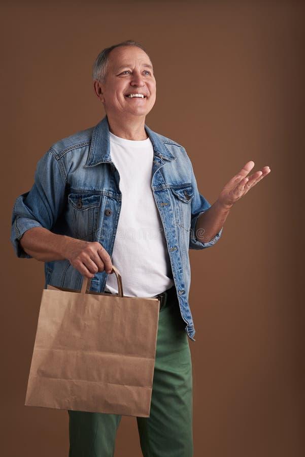Lycklig man som ser upp och ler medan anseende med papperspåsen arkivfoto