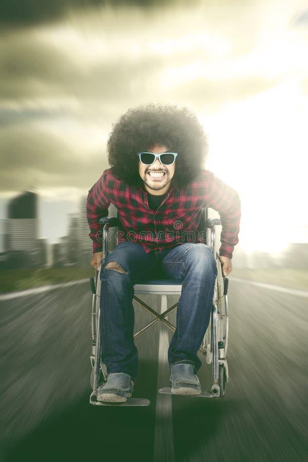 Lycklig man som sitter i rullstol med snabb rörelse royaltyfria bilder