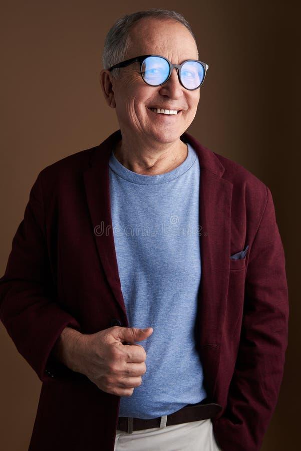 Lycklig man som trycker på hans rödbruna omslag och le arkivfoton