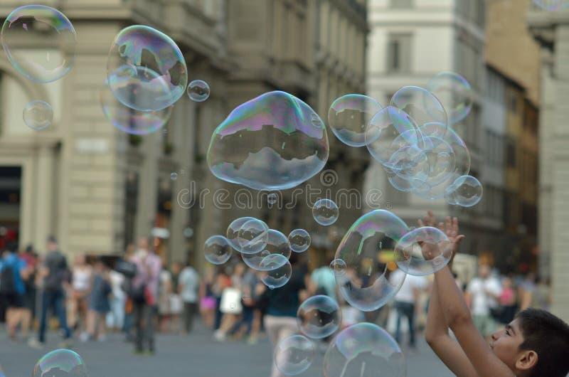 Lycklig man som underhåller turister och medborgare med flygsåpbubblor i den gamla mitten av arkivfoton