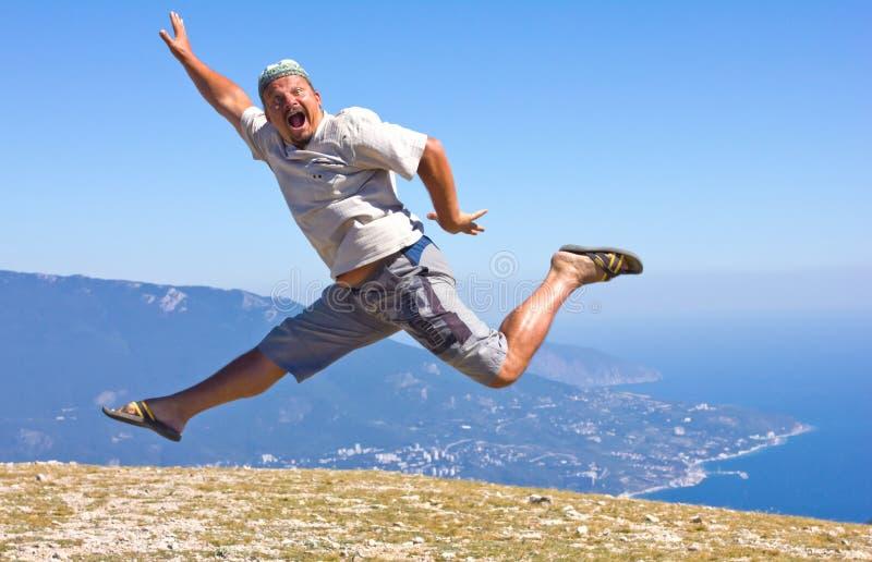 Lycklig manbanhoppning över berg, skyen och havet arkivbilder