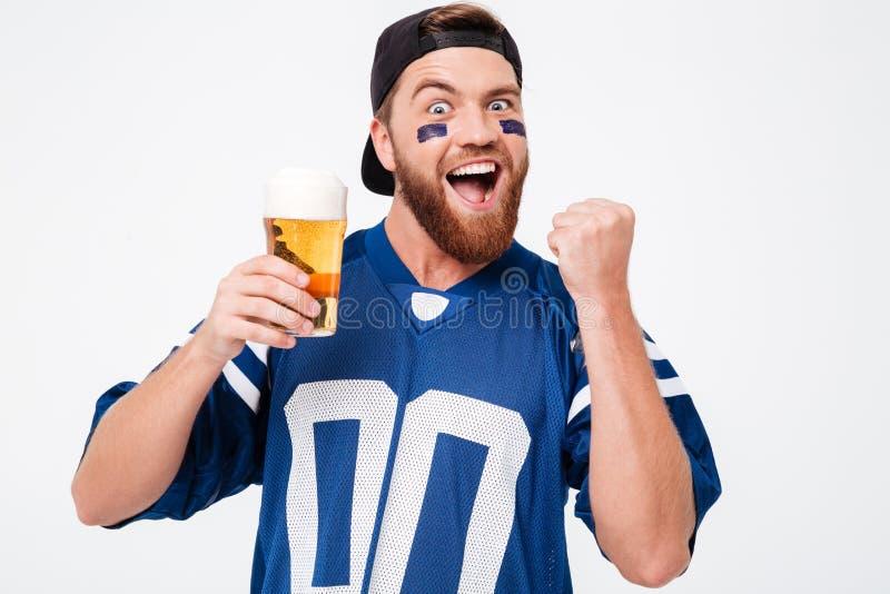 Lycklig manfan i blå t-skjorta som dricker öl royaltyfria bilder