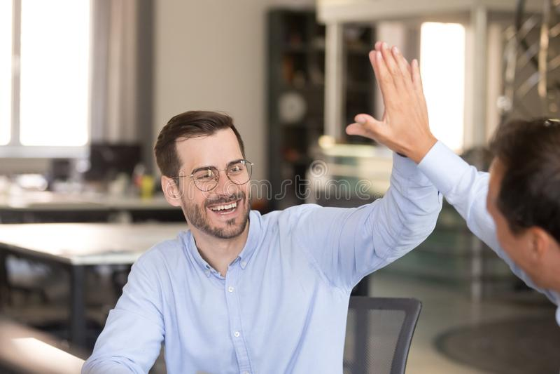 Lycklig manlig anställd som ger högt fem till kollegan royaltyfri fotografi