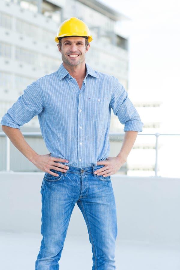 Lycklig manlig arkitekt med händer på höfter arkivbild