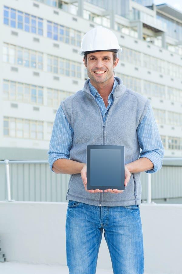 Lycklig manlig arkitekt som utomhus visar den digitala minnestavlan arkivfoto