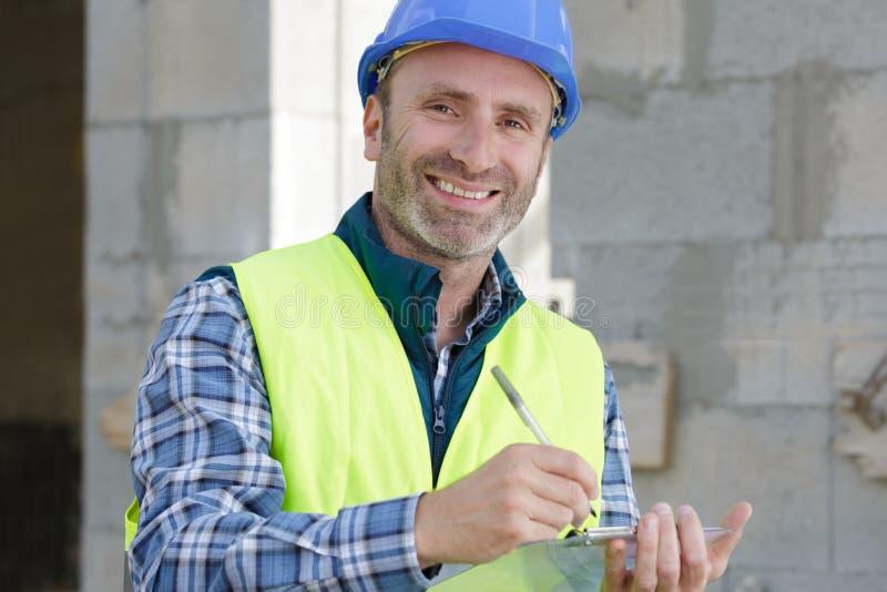 Lycklig manlig byggmästare i hård hatt med skrivplattan royaltyfri fotografi