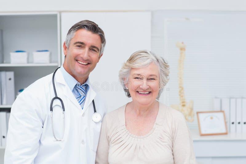 Lycklig manlig doktors- och kvinnligpatient i klinik arkivbild