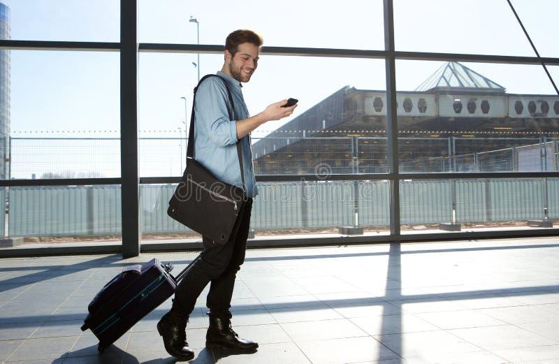 Lycklig manlig handelsresande som går med påsar och mobiltelefonen arkivbilder