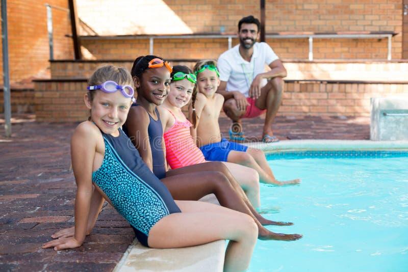 Lycklig manlig instruktör och barn som kopplar av på poolsiden arkivbild