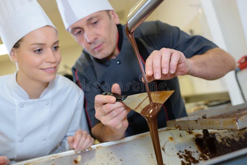 Lycklig manlig kock och kvinnlig kock som förbereder efterrätten arkivfoto