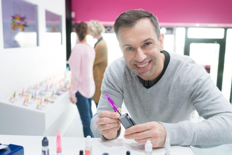 Lycklig manlig kund som väljer e-cigaretten arkivbild