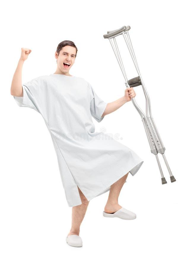 Lycklig manlig patient i hållande kryckor för sjukhuskappa royaltyfri foto