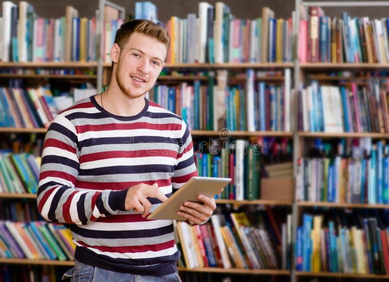 Lycklig manlig student som använder en minnestavladator i ett arkiv arkivbilder