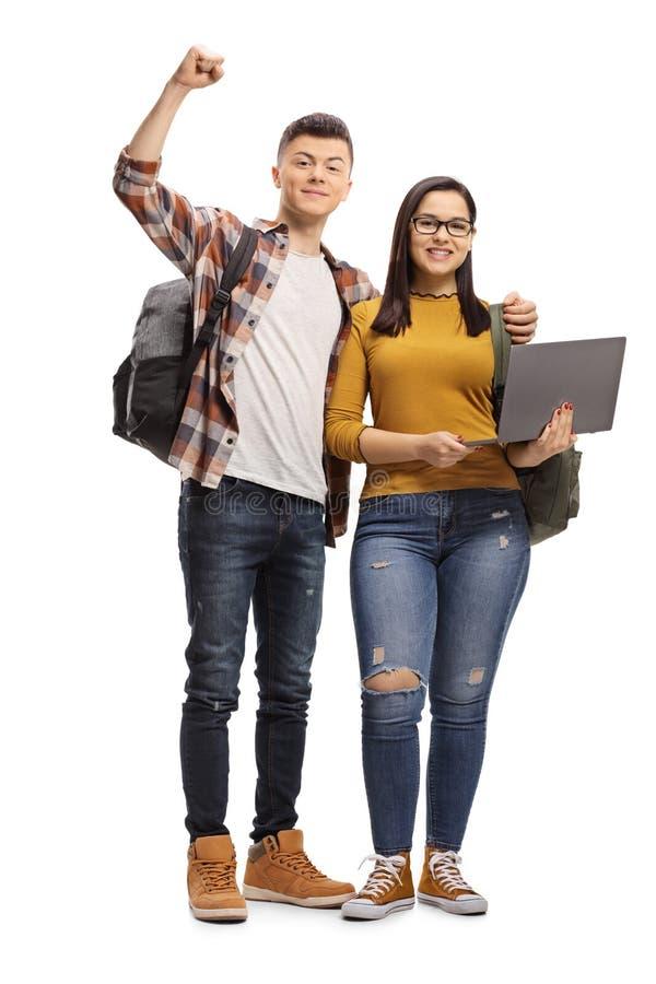 Lycklig manlig student som omfamnar ett anseende för kvinnlig student och rymmer en bärbar datordator royaltyfri foto
