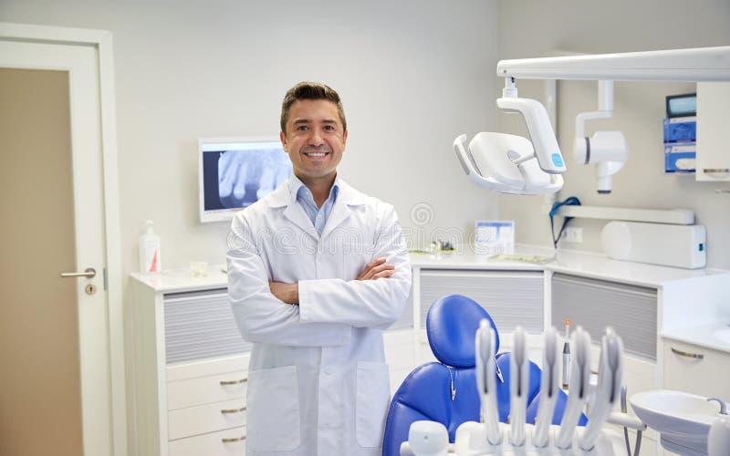 Lycklig manlig tandläkare på det tand- klinikkontoret royaltyfri foto