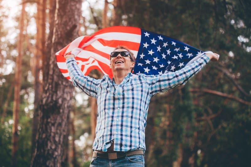 Lycklig manspring med USA flaggan Fira självständighetsdagen av Amerika Juli 4th gyckel som har mannen royaltyfri bild